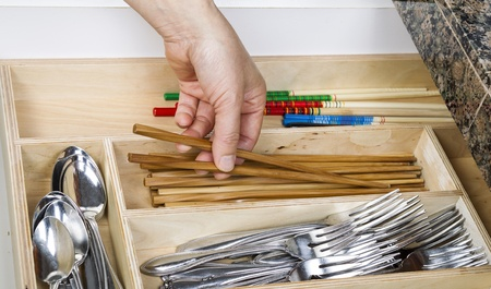 Female hand picking up wooden chop sticks out of kitchen drawer