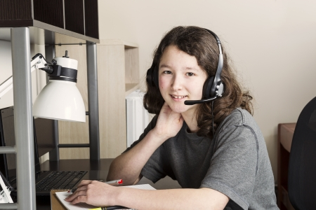 preteen asian: Young girl doing homework with headset on while sitting at her desk