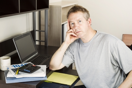 Mature man preparing to do income taxes with computer, calculator, booklet and coffee on desk  photo