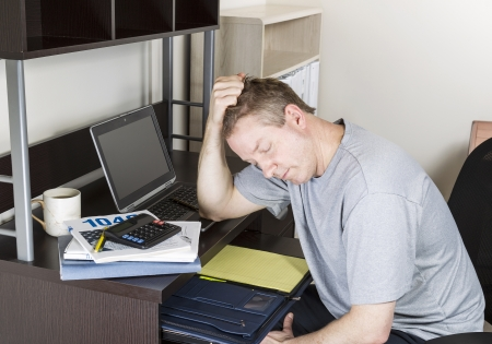Mature man holding head in hand with computer, tax income booklet and coffee cup on desk  photo