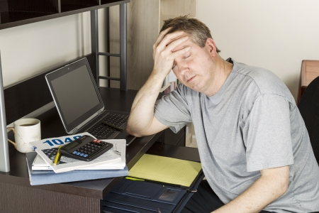 income tax: Mature man holding head in hand with computer, calculator, tax income booklet and coffee cup on desk Stock Photo