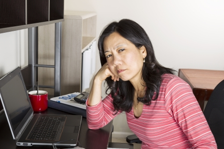 Mature Asian woman tired of doing income taxes with tax form booklet, calculator, coffee cup and computer on desk Stock Photo