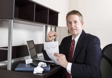 cpa: Mature man holding pen in clenched fist with computer, calculator, and papers on desk