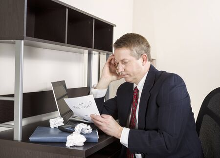 Mature man holding pen in hand against head with computer, calculator, and papers on desk photo