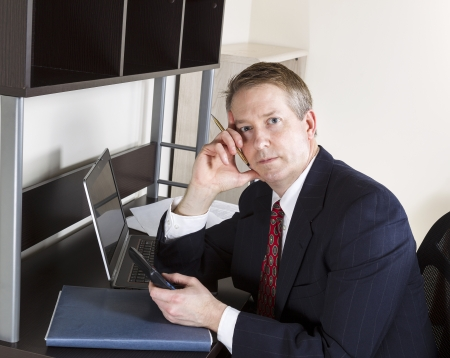 Mature man holding calculator while thinking with computer and papers on desk  photo