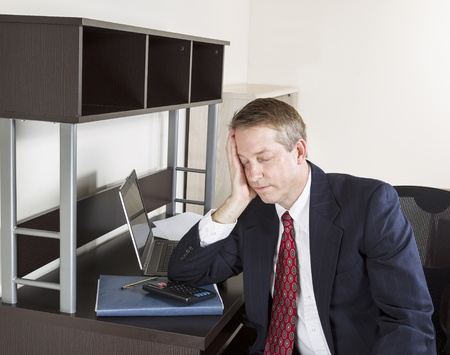 Mature man resting head in hand with calculator, computer, papers and pen on desk Stock Photo - 17097243