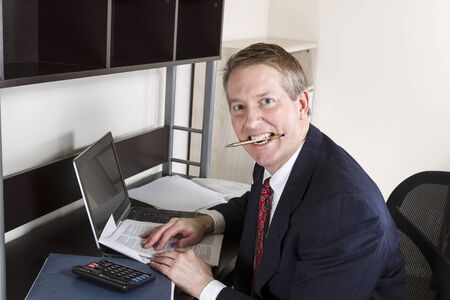 Mature man chewing pen while working on income tax with calculator, computer and papers on desk  photo