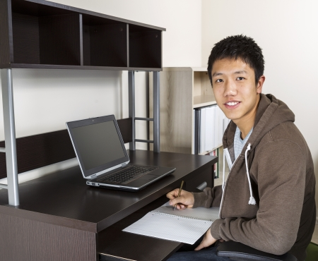 Young Adult Man with pen and paper in hand with computer on desk and wall in background  photo