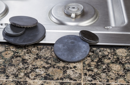 Elegant Natural Gas Stove Burner Covers Removed For Cleaning With Pilot Light And  Stove Top In Background