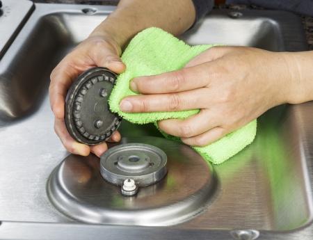 estufa: Las manos con un paño de limpieza de microfibra tapa del quemador de gas estufa