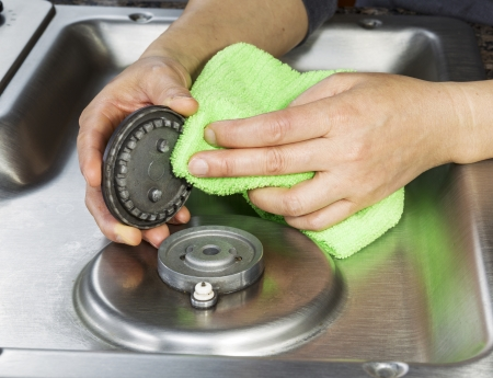 Hands with microfiber cloth cleaning gas stove burner cover Archivio Fotografico