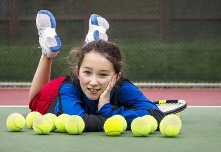 tenis: Horizontal Retrato de la sonrisa adolescente jugador de tenis joven que pone en la cancha detrás de una hilera de bolas de tenis con la cabeza apoyada en la mano y los pies en el aire