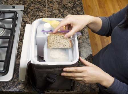 Female hands packing lunch into portable bag while in the kitchen on stone counter top next to stove photo