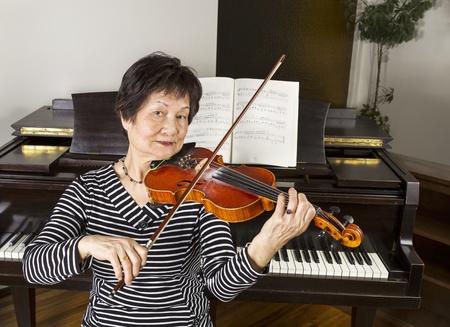 수석 성인 여자는 백그라운드에서 피아노와 함께 집에서 바이올린을 연주