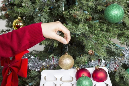 storing: Female hand putting away Golden holiday ornament into white card board box to end the season