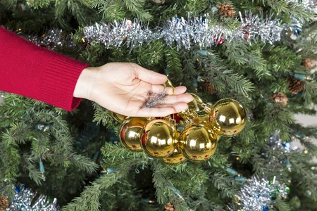 Female hand gathering golden ornaments to be put into storage with Christmas tree in background Stock Photo - 17360542