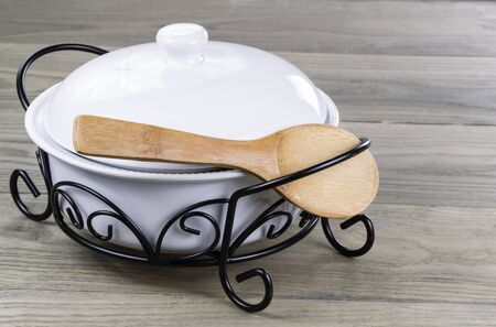 Traditional serving pot with wooden spoon on Stressed wooden table