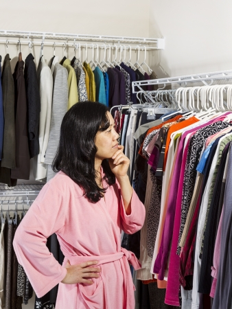 Vertical portrait of mature Asian woman, dressed in pink bath robe, inside of walk-in closet deciding what to wear for the day