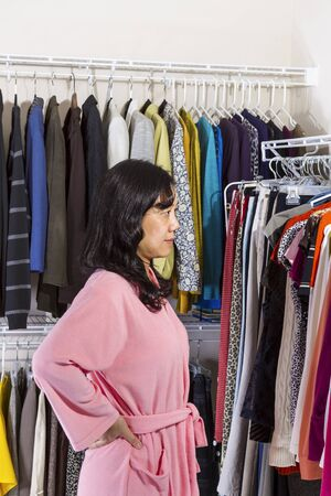 walk in closet: Vertical portrait of mature Asian women, dressed in pink bath robe, standing in walk-in closet while looking at clothing  Stock Photo