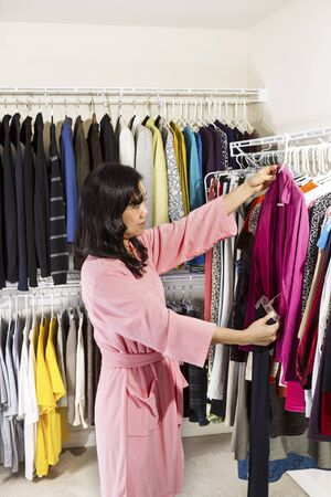 Vertical portrait of mature Asian woman, dressed in pink bath robe, in walk-in closet inspecting her clothing before wearing Stock Photo - 17538639