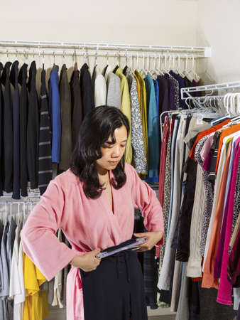 walk in closet: Vertical portrait of mature Asian woman, dressed in pink bath robe, in walk-in closet checking her waist size with pants next to her body