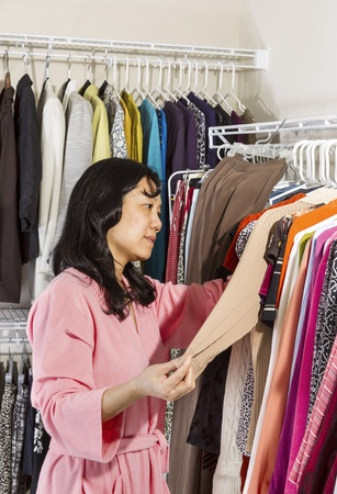 Vertical portrait of mature Asian woman, dressed in pink bath robe, in walk-in closet inspecting her sweater before wearing Stock Photo - 17538656