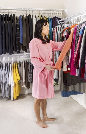 Full vertical portrait shot of mature Asian woman, dressed in pink bath robe, in walk-in closet selecting her clothing in morning  Stock Photo - 17538660