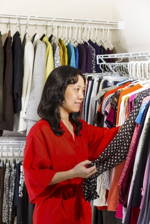 Vertical portrait of mature Asian woman, dressed in red bath robe, in walk-in closet inspecting her clothing before wearing Stock Photo - 17538647