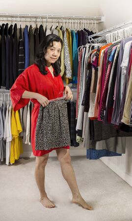 Full vertical portrait of mature Asian woman, dressed in red bath robe, in walk-in closet placing mini skirt next to her waist Stock Photo - 17538644