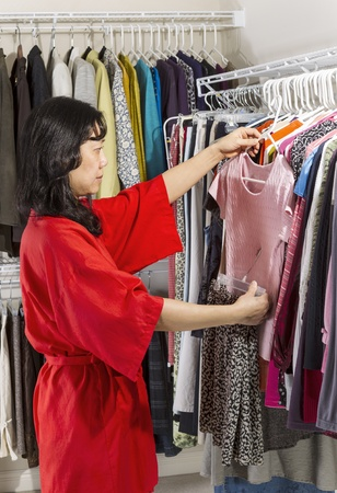 Vertical portrait of mature Asian woman, dressed in red bath robe, in walk-in closet coordinating her clothes