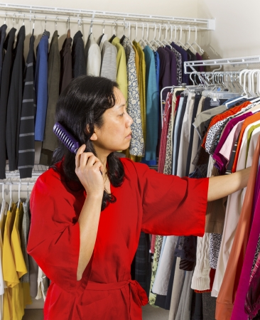 Vertical portrait of mature Asian woman, dressed in red bath robe, in walk-in closet combing her hair while looking at her hanging clothes