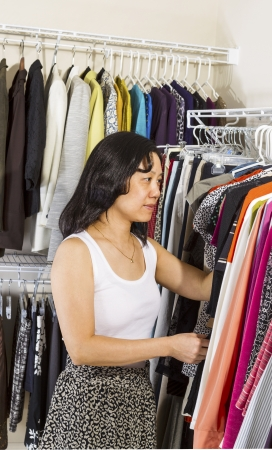 Vertical portrait of mature Asian woman selecting clothes while dressing in walk-in closet
