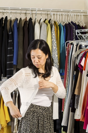 Vertical portrait of mature Asian woman in walk-in closet inspecting her white sweater  Stock Photo