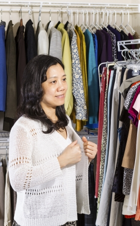 Vertical portrait of mature Asian woman in walk-in closet putting on her white sweater  photo