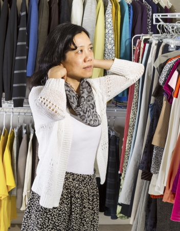 Vertical portrait of mature Asian woman in walk-in closet putting on her scarf Stock Photo - 17538638