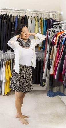 walk in closet: Full vertical portrait of mature Asian woman in walk-in closet putting on her scarf