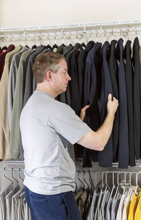 Vertical portrait of mature man in walk-in closet inspecting his sweater for daily wear  Stock Photo - 17566651