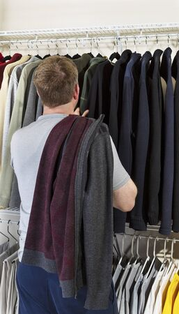 walk in closet: Vertical portrait of mature man in walk-in closet over looking his sweaters for wearing