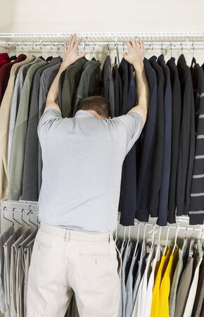 Vertical portrait of mature man in walk-in closet sticking his head in sweaters due to being tired