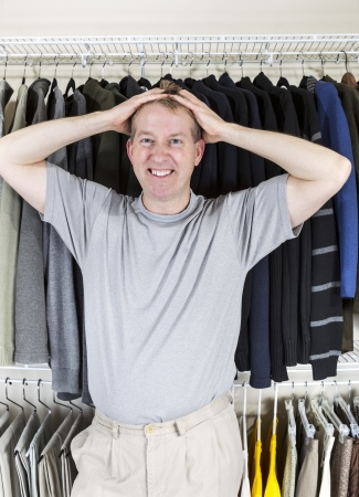 walk in closet: Vertical portrait of mature Caucasian man in walk-in closet showing frustration with hands behind head while pulling his hair  Stock Photo