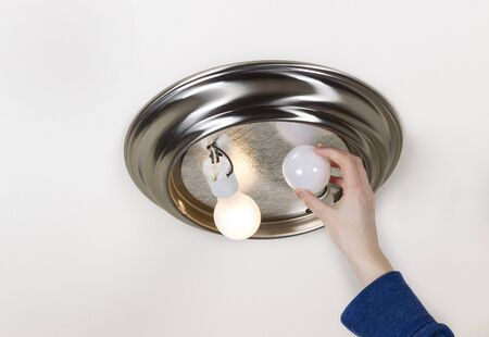 incandescent: Horizontal photo of hand taking out light bulb- incandescent type- with one bulb burnt out and one working