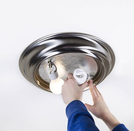 Photo female hands installing compact fluorescent bulb to replace incandescent type bulb
