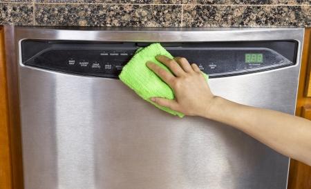 여성의 손은 마이크로 화이버 타월로 스테인레스 스틸 식기 세척기의 앞 부분을 닦아