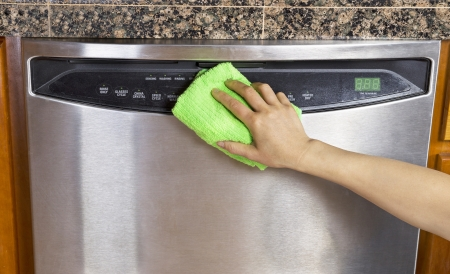 Female hand wiping down front part of stainless steel dishwasher with microfiber towel  Stock Photo