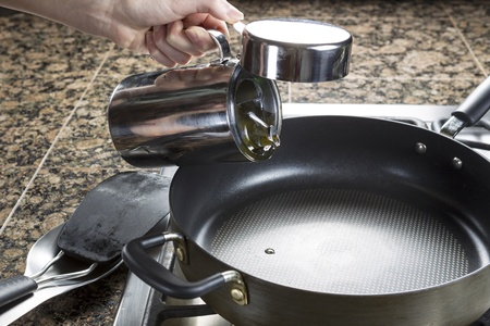 Photo of female hand adding cooking oil to frying pan in preparation of making breakfast Stock Photo - 17794646