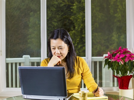 thinking woman: Mature Asian woman working at home with notebook computer on glass table with large windows behind with visible evergreen trees in background  Stock Photo