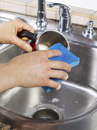Vertical photo of female hands cleaning a coffee mug with soapy water and a sponge with kitchen sink in background Stock Photo - 18061068