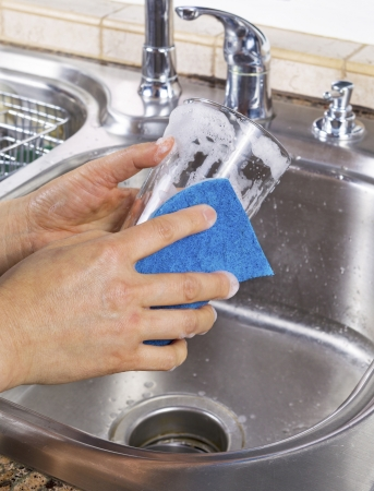 soapy: Vertical photo of female hands cleaning a drinking glass with soapy water and a sponge with kitchen sink in background Stock Photo