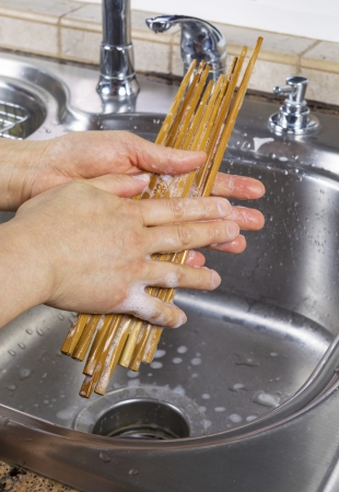Vertical photo of female hands cleaning bamboo chopsticks with soapy water along with kitchen sink and faucet in background Stock Photo - 18061064