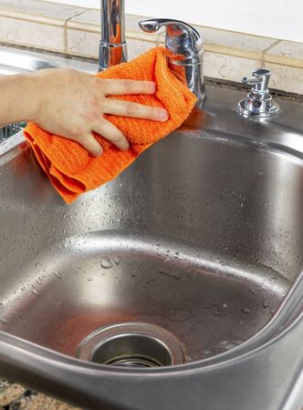 Vertical photo of female hand drying off kitchen sink with microfiber towel